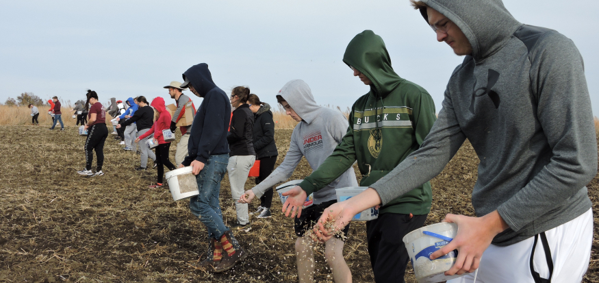 Students hand sow native seed at Irvine Prairie.